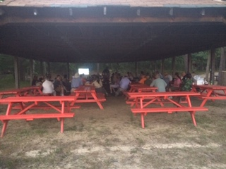 A crowd of people sitting at red picnic tables