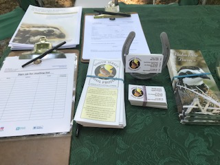 South Jersey Quail Project brochures, business cards, and sign up sheets sitting on a green tablecloth.