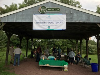 A picture of a pavilion with a sign on it that says Wildlife Sanctuary. Underneath the pavilion is a group of people conversing.